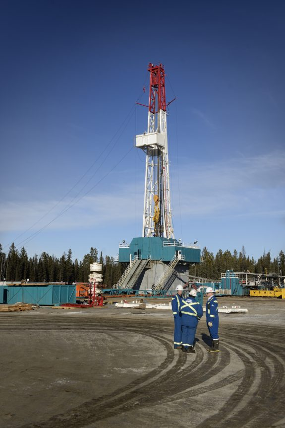 Workers standing in front of a drilling rig